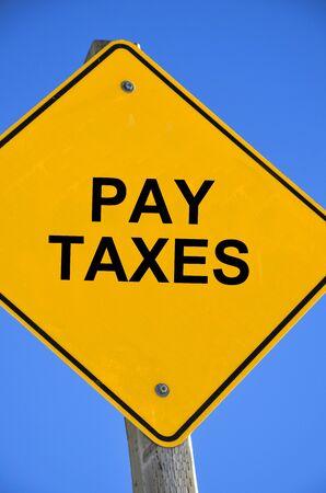 Een afbeelding van een helder geel verkeersbord met de tekst 'Belastingen betalen'.