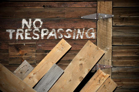 trespassing: An image of No Trespassing written in white on the side of an old weathered barn.