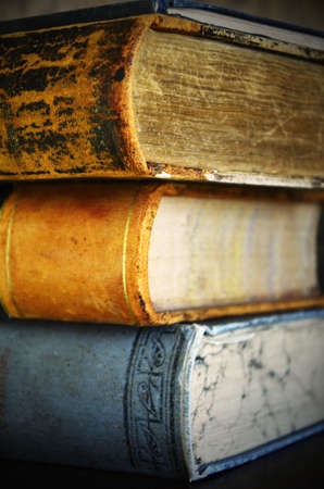 book binding: A close up image of a stack of old vintage books.