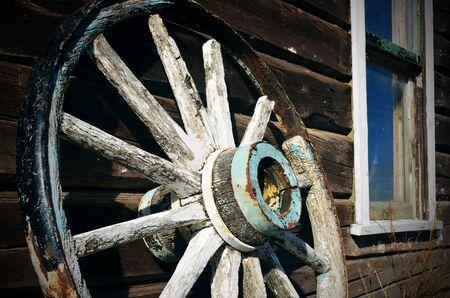 carreta madera: Una imagen de una vieja rueda de carro de madera apoyado en un edificio. Foto de archivo