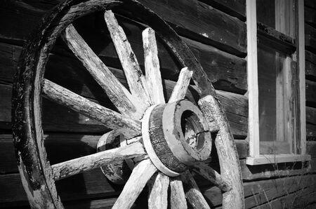 carreta madera: Una imagen en blanco y negro de una vieja rueda de carro de madera apoyado en un edificio. Foto de archivo
