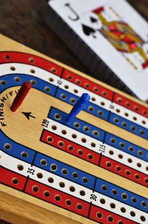 A low angle image of a cribbage board and pegs with the jack of spades in the background.