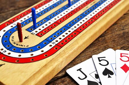 low angle: A low angle image of a cribbage board and pegs.