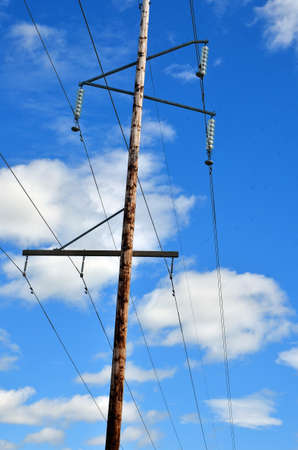 power pole: An image of a power pole and power lines against a blue sky. Stock Photo