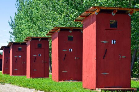 outhouse: An image of five public out houses in a row.