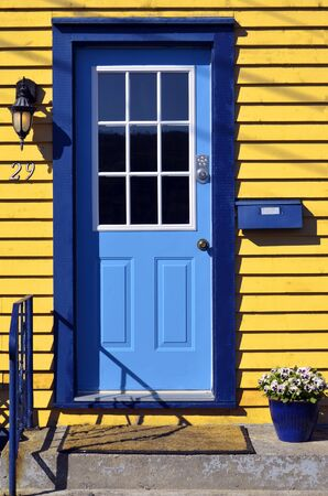 hand rail: An image of a blue door on a bright yellow house. Stock Photo