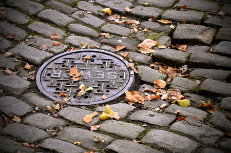 An abstract image of a sewer lid on an old brick street.