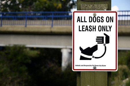 An image of a sign which indicates all dogs must be on a leash. Stock Photo