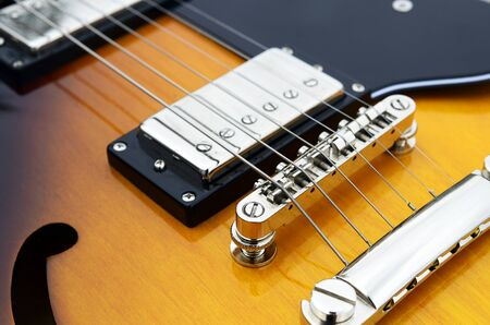 close up image: A close up image of a yellow electric guitar.