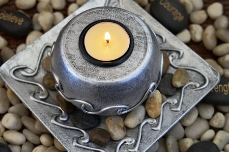 tea light: A top view image of a lite tea light candle on a metal candle holder surrounded by pebbles. Stock Photo