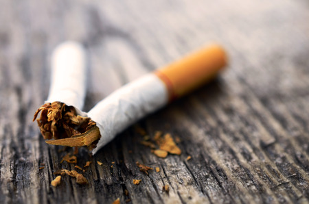 quiting smoking: A close up image of a single broken cigarette on a wooden table top.