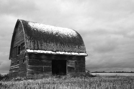 run down: An black and white image of an old run down barn with snow on the roof and storm clouds in the background.