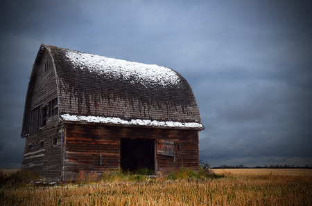 run down: An image of an old run down barn with snow on the roof and storm clouds in the background.
