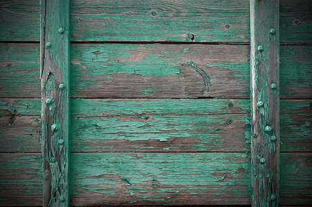 peeling paint: An image of old weathered wood with green peeling paint.