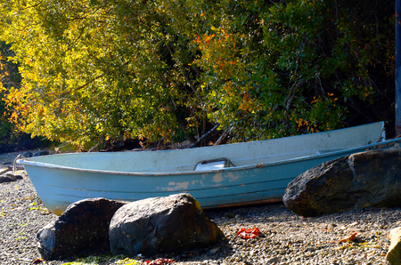 An image of an old blue boat up on shore.