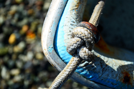 An abstract image of a knotted rope on an old small fishing boat. Stock Photo