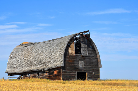 damaged roof: An image of an old weathered and abandoned barn. Stock Photo