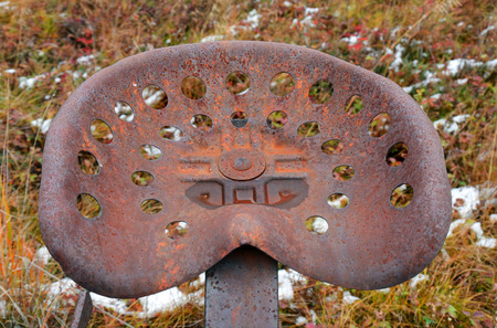 drivers seat: An image of an antique metal tractor seat.