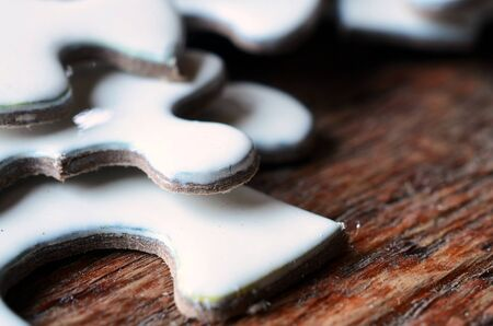 A close up view of several white jigsaw puzzle pieces on a wooden table top.