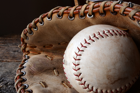 catcher's mitt: A close up image of an old used baseball and baseball glove.