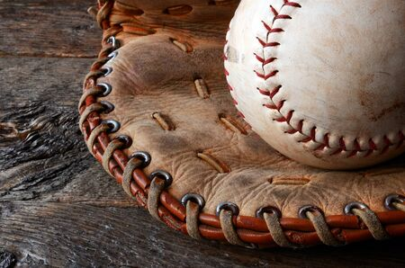 catcher's mitt: A close up image of an old used baseball and leather baseball glove.