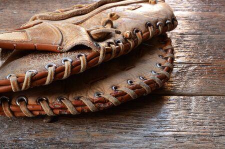 木製テーブルの上に古い使用される野球グローブのイメージに近い。 写真素材