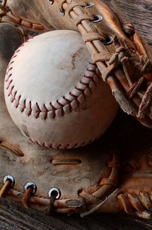 catcher's mitt: A top view image of an old used baseball and leather baseball glove.