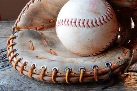 catcher's mitt: A low angle image of an old used baseball and leather baseball glove.