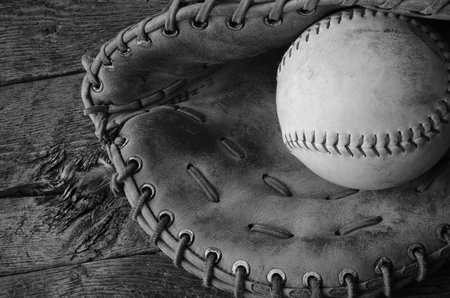 catcher's mitt: A black and white image of an old used baseball and baseball glove.