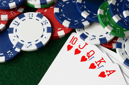 A top view image of poker chips and cards on a poker table. Stock Photo