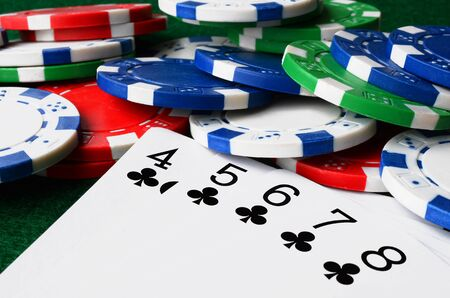 high stakes: A low angle image of poker chips and cards on a poker table. Stock Photo