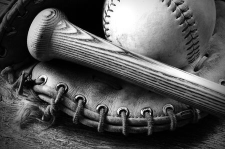 catcher's mitt: A black and white image of an old catchers mitt and bat.