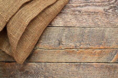 An abstract image of folded burlap fabric and wood texture. Banco de Imagens