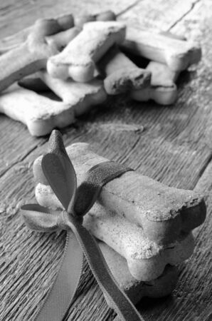 large dog: A close up image of several large bone shaped dog treats on a wooden table.