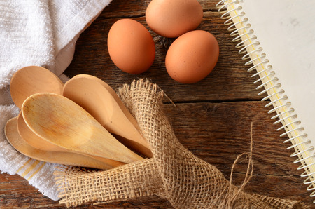 A top view image of wooden mixing spoons, brown eggs, and an old cookbook on a kitchen table.
