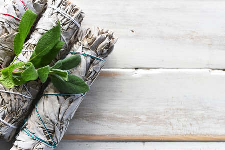 A top view image of white sage smudge bundles with fresh white sage leaves on a white wooden background.