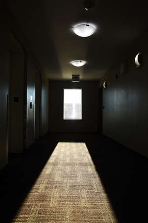 An image of sunlight streaming through a window in a very dark hallway of a run down apartment building.