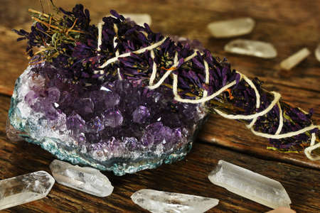 A close up image of an amethyst geode and lilac smudge stick with clear quartz crystals on a dark wooden desk top.