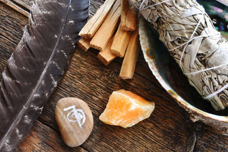 A top view image of white sage smudge stick with healing crystals, sacred feather and reiki symbol. Standard-Bild