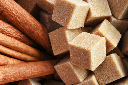 A close up image of brown sugar cubes and cinnamon sticks.
