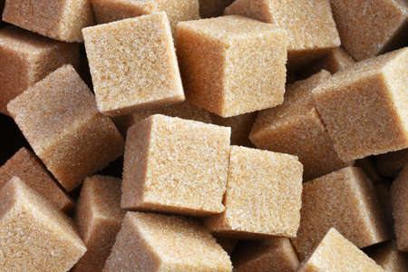 A close up image of several brown sugar cubes in an hand made pottery bowl.