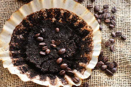 A close up image of used coffee ground and coffee filter on brown burlap fabric.
