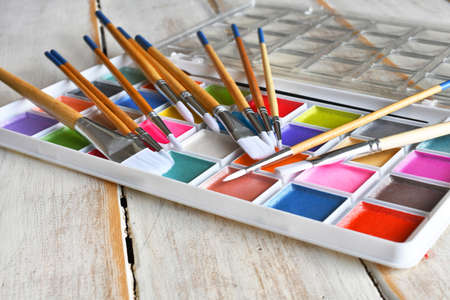 A close up image of a brightly colored set of water color paints with paint brushes.