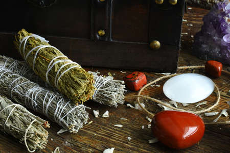 A close up image of a variety of sacred smudge bundles with selenite and red jasper crystals on a dark wooden table top.