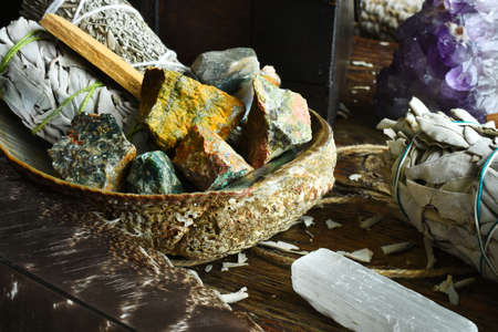 A close up image of several different smudge bundles with selenite and healing crystals in an abalone shell.