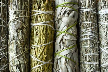 A top view image of several healing sage smudge bundles on burlap fabric.