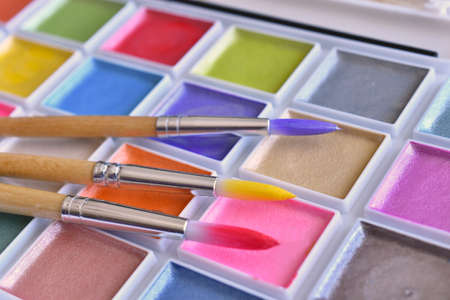 A close up image of brightly colored water paints and paint brushes.