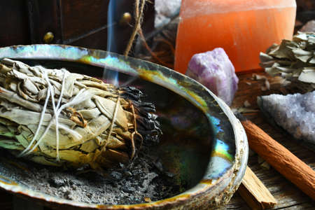 A close up image of a burning white sage smudge stick with selenite candle.
