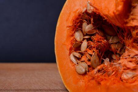 Cut pumpkin with seeds on a wooden board. Pumpkin on dark background. Vegetable. Melons. Food.