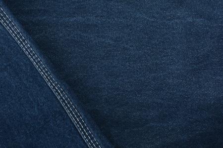 Texture denim. Dense tissue. Textiles. Background. Dark blue natural fabric.